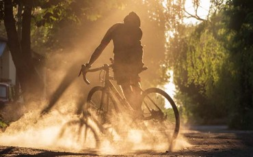 Cyclist riding a bicycle on a gravel road at sunset. A silhouette of young sporty man on a gravel bike in a cloud of dust from real whell after skidding.